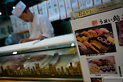 A man prepares sushi behind the counter of a small restaurant in the area of the Tokyo fish market