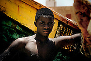 A Mauritanian teen fisherman suns himself to dry off amid colorfully painted fishing boats after returning from a morning at sea to the fishing market in the Mauritanian capital of Noukchott May 20, 2008.