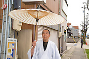 A Japanese man in traditional clothes and parasol
