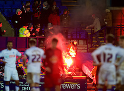 BIRKENHEAD, ENGLAND - Saturday, January 3, 2015: A steward picks up a red flare, set off by Swansea City supporters as they celebrate their side's 6-2 victory over Tranmere Rovers, during the FA Cup 3rd Round match at Prenton Park. (Pic by David Rawcliffe/Propaganda)