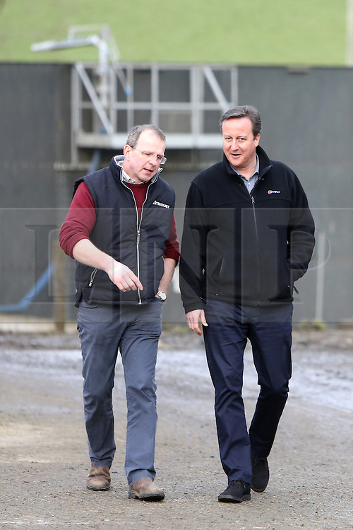 Licensed to London News Pictures. 27/02/2016. Ahoghill, County Antrim, Northern Ireland. UK. Prime Minister David Cameron (R)walks with Farmer Harry Johnston during a tour of his dairy farm in County Antrim. The Prime Minister was on a tour to persuade voters that membership of a reformed EU is in their best interests. Photo credit : Paul McErlane/LNP