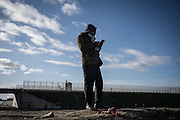 A migrant is seen talking at the phone in the Calais refugges camp. Calais, France. FEDERICO SCOPPA/CAPTA