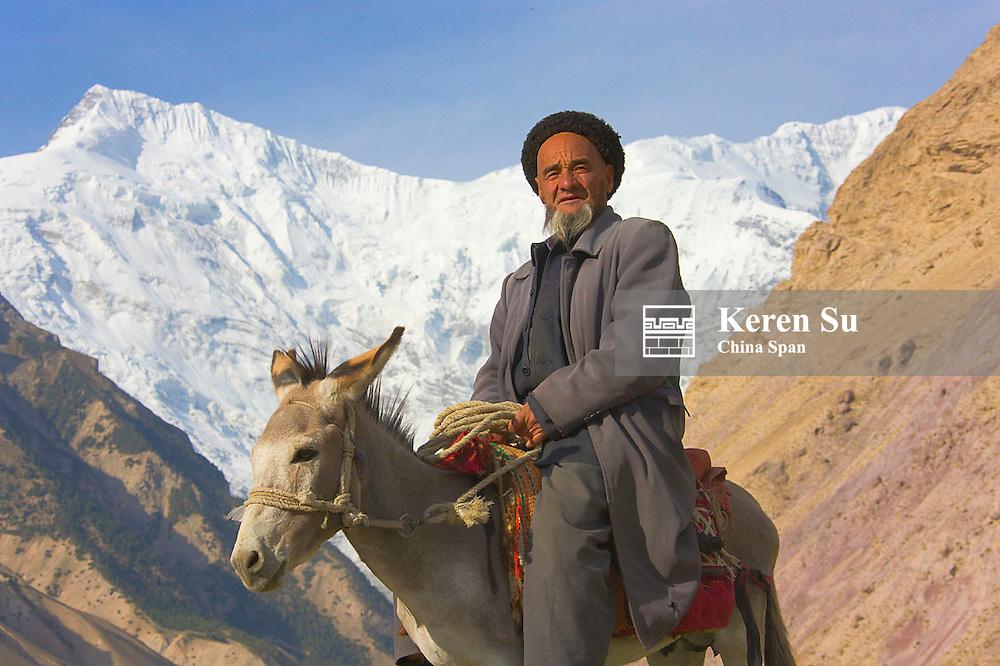 Tajik man on donkey with Aoyitage peak, Pamir Plateau, Xinjiang, China