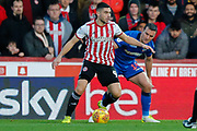 Brentford attacker Neal Maupay (9) battles with Bolton Wanderers defender Jack Hobbs (14) during the EFL Sky Bet Championship match between Brentford and Bolton Wanderers at Griffin Park, London, England on 22 December 2018.