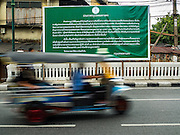 11 OCTOBER 2015 - BANGKOK, THAILAND:  A tuk-tuk (three wheeled taxi) goes past a government posting announcing the closing of Saphan Lek and Saphan Han markets in Bangkok. The two markets are across the street from each other Many shops in the markets are already closed. Street vendors and illegal market vendors in the Saphan Lek and Saphan Han will be removed in the next two weeks as a part of an urban renewal project coordinated by the Bangkok Metropolitan Administration. About 500 vendors along Damrongsathit Bridge, popularly known as Saphan Lek, have until Monday, October 11,  to relocate. Vendors who don't move will be evicted. Saphan Lek is one of several markets and street vending areas being closed in Bangkok this year. The market is known for toy and replica guns, bootleg and pirated DVDs and CDs and electronic toys.   PHOTO BY JACK KURTZ