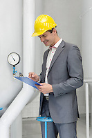 Smiling young male manager writing on clipboard in industry