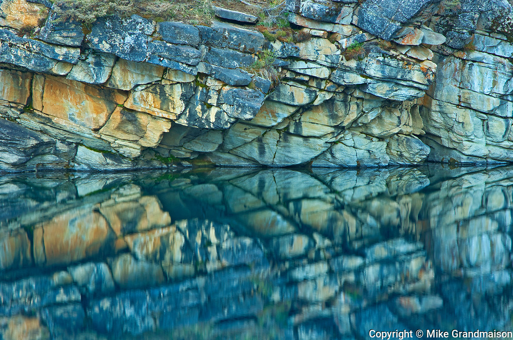 Reflection of rock cliff in Horseshoe Lake, Jasper National Park, Alberta, Canada