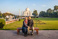 A western couple sits posing for a photo in front of the Taj Mahal in Agra, Uttar Pradesh,  India.