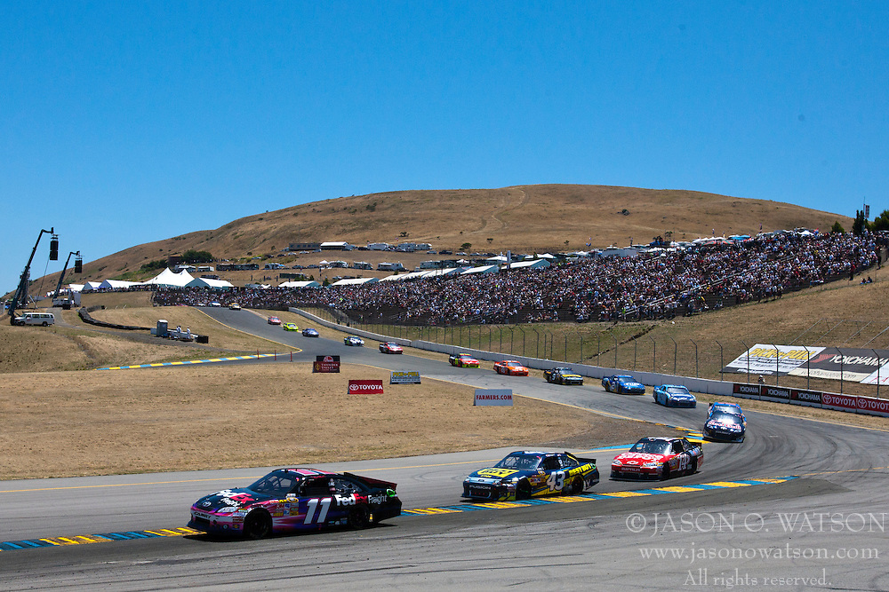 June 26, 2011; Sonoma, CA, USA;  NASCAR Sprint Cup Series driver Denny Hamlin (11) and driver A.J. Allmendinger (43) drive at the front of the field in turn 4 during the Toyota/Save Mart 350 at Infineon Raceway.