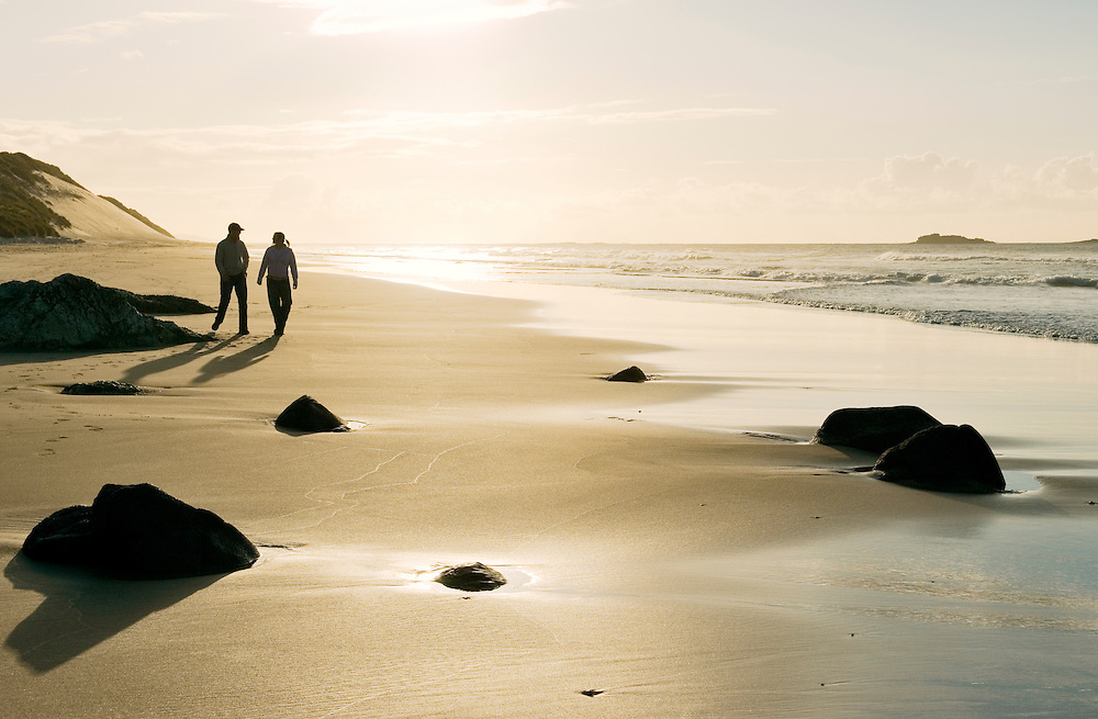Young couple boy girl man woman walking along sandy beach shoreline evening light summer with footprints in the sand. Ireland.