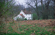 AF5GXB Remote white country cottage in woodland in winter Butley Suffolk England