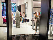 "27 MARCH 2015 - BANGKOK, THAILAND:  A worker in a Diane von Fürstenberg store in ""EmQuartier,"" a new shopping mall in Bangkok, cleans the glass door before the store's opening. ""EmQuartier"" is across Sukhumvit Rd from Emporium. Both malls have the same corporate owner, The Mall Group, which reportedly spent 20Billion Thai Baht (about $600 million US) on the new mall and renovating the existing Emporium. EmQuartier and Emporium have about 450,000 square meters of retail, several hotels, numerous restaurants, movie theaters and the largest man made waterfall in Southeast Asia. EmQuartier celebrated its grand opening Friday, March 27.   PHOTO BY JACK KURTZ"