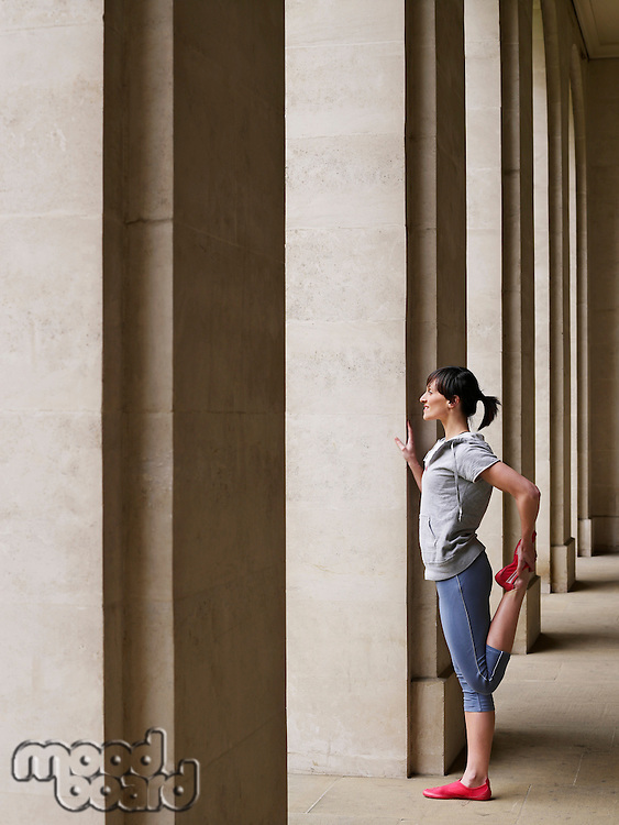 Woman stretching in portico side view