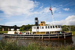 "© Licensed to London News Pictures. 30/09/2016. Bartington UK. Picture shows the Daniel Adamson making it's way along the River Weaver on it's maiden voyage after a £5M renovation. The Daniel Adamson steam boat has been bought back to operational service after a £5M restoration. The coal fired steam tug is the last surviving steam powered tug built on the Mersey and is believed to be the oldest operational Mersey built ship in the world. The ""Danny"" (originally named the Ralph Brocklebank) was built at Camel Laird ship yard in Birkenhead & launched in 1903. She worked the canal's & carried passengers across the Mersey & during WW1 had a stint working for the Royal Navy in Liverpool. The ""Danny"" was refitted in the 30's in an art deco style. Withdrawn from service in 1984 by 2014 she was due for scrapping until Mersey tug skipper Dan Cross bought her for £1 and the campaign to save her was underway. Photo credit: Andrew McCaren/LNP"