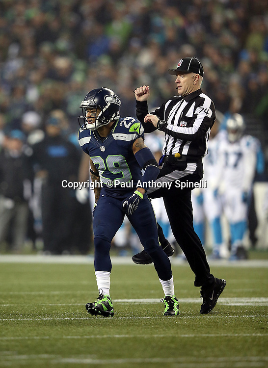 Referee Terry McAulay (77) runs toward the play as he appears to kick Seattle Seahawks free safety Earl Thomas (29) in the behind on a second quarter play during the NFL week 19 NFC Divisional Playoff football game against the Carolina Panthers on Saturday, Jan. 10, 2015 in Seattle. The Seahawks won the game 31-17. ©Paul Anthony Spinelli