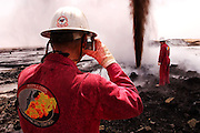 Boots and Coots firefighters photograph each other near a raging oil gusher in Rumaila oil field, Southern Iraq. The Rumaila field is one of Iraq's biggest with five billion barrels in reserve. Boots and Coots had a team of firefighters in Kuwait ready to go into Iraq several weeks before the war began. All of their equipment (including bulldozers and trucks) was flown in from Texas on large Russian cargo planes (AN-124s). Rumaila is also spelled Rumeilah.