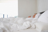 Mature woman lying in bed with thermometer in mouth side view