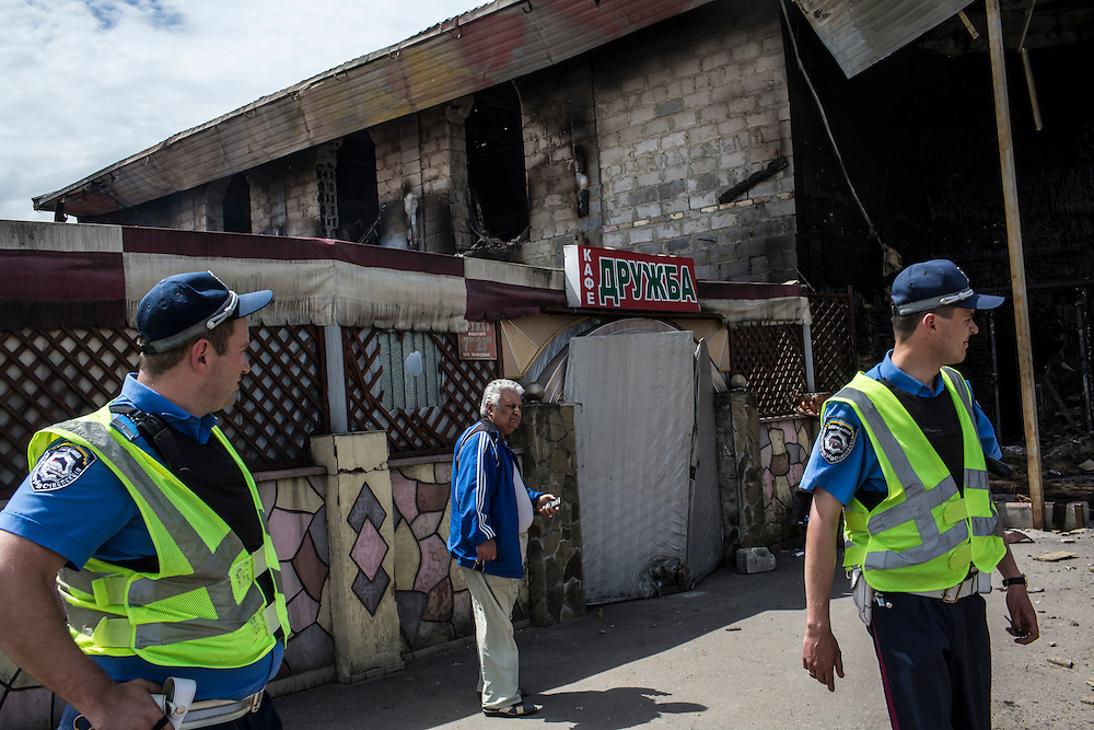 KARLIVKA, UKRAINE - MAY 23: Police and local residents check out the scene of an early morning firefight between the pro-Ukraine Donbass Battalion and the pro-Russia Vostok Battalion militias on May 23, 2014 in Karlivka, Ukraine. At least eight people between the two sides, including one civilian, were killed in an early morning firefight when the Donbass Battalion, a pro-Ukraine militia, attacked a Vostok Battalion checkpoint in the nearby town of Karlivka. (Photo by Brendan Hoffman/Getty Images) *** Local Caption ***