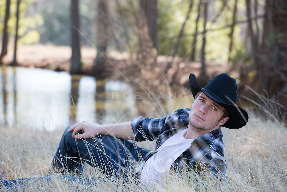 cowboy relaxing in tall grass on a ranch with a pond