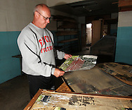 Ed Thomas, of Parkersburg, a teacher and football coach at Aplington-Parkersburg High School looks at an old team photo he saved from the school building in Parkersburg, Iowa on Wednesday June 4, 2008. (Stephen Mally for the New York Times)