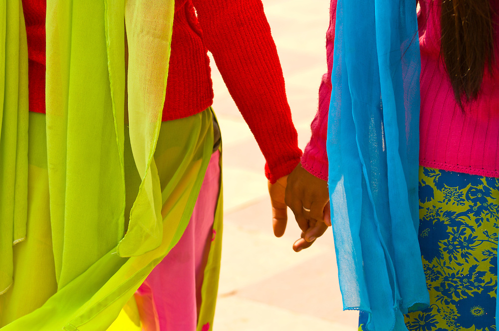 Indian women in colorfuls saris walking and holding hands, the Taj Mahal, Agra, Uttar Pradesh, India