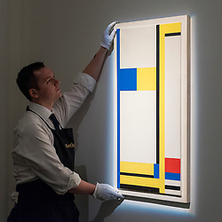 "© Licensed to London News Pictures. 18/11/2016. London, UK. A technician examines ""Composition Yellow, Blue, Black, Red and White"" by Marlow Moss (est. GBP60-80k), at the preview at Sotheby's of works on view at four upcoming November auctions featuring Modern & Post-War British Art, A Painter's Paradise (Julian Trevelyan & Mary Fedden at Durham Wharf), Scottish Art and Picasso Ceramics from the Lord & Lady Attenborough Private Collection. Photo credit : Stephen Chung/LNP"