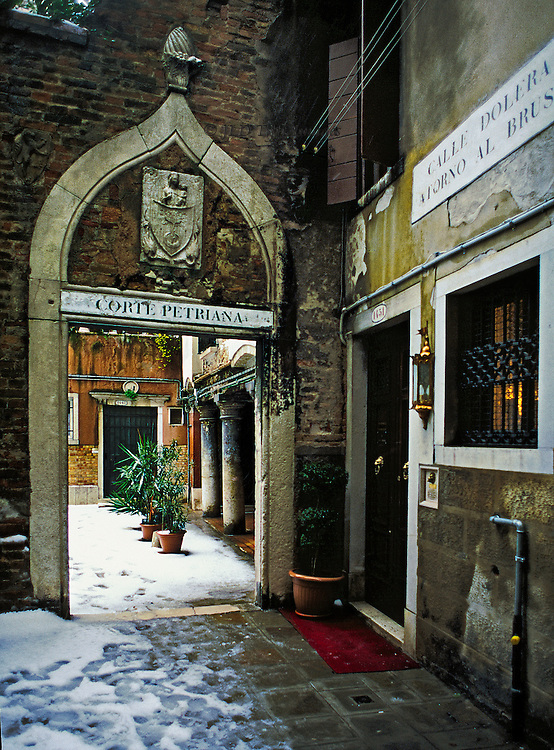View into Corte Petriana past the Ca' Arco Antico (bed and breakfast), San Polo district, Venice, on a snowy day with slush underfoot.