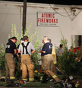 07 September 2010: Fire fighters debrief after putting out a fire at Atomic Fireworks near the intersection of West Bypass and Sunshine. The current cause is unknown. Credit: David Welker / TurfImages.com