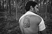 A Roma berry picker from Bulgaria reveals a tattoo of Jesus on his back in the forest between the towns of Katrineholm and Vingåker in Sweden. He is an Evangelical Christian.