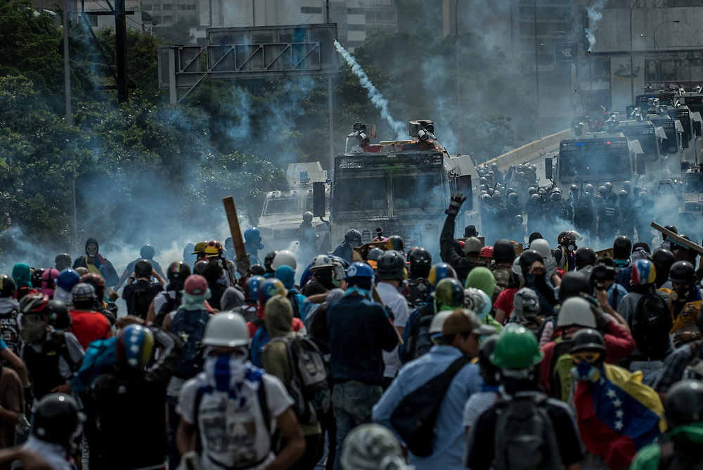 CARACAS, VENEZUELA - MAY 22, 2017:  National guard soldiers fire  tear gas, rubber bullets and buckshot at anti-government protesters who had taken over the Francisco Fajardo highway - the main highway that runs through Caracas. The streets of Caracas and other cities across Venezuela have been filled with tens of thousands of demonstrators for nearly 100 days of massive protests, held since April 1st. Protesters are enraged at the government for becoming an increasingly repressive, authoritarian regime that has delayed elections, used armed government loyalist to threaten dissidents, called for the Constitution to be re-written to favor them, jailed and tortured protesters and members of the political opposition, and whose corruption and failed economic policy has caused the current economic crisis that has led to widespread food and medicine shortages across the country.  Independent local media report nearly 100 people have been killed during protests and protest-related riots and looting.  The government currently only officially reports 75 deaths.  Over 2,000 people have been injured, and over 3,000 protesters have been detained by authorities.  PHOTO: Meridith Kohut