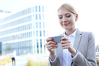 Businesswoman text messaging through smart phone outdoors