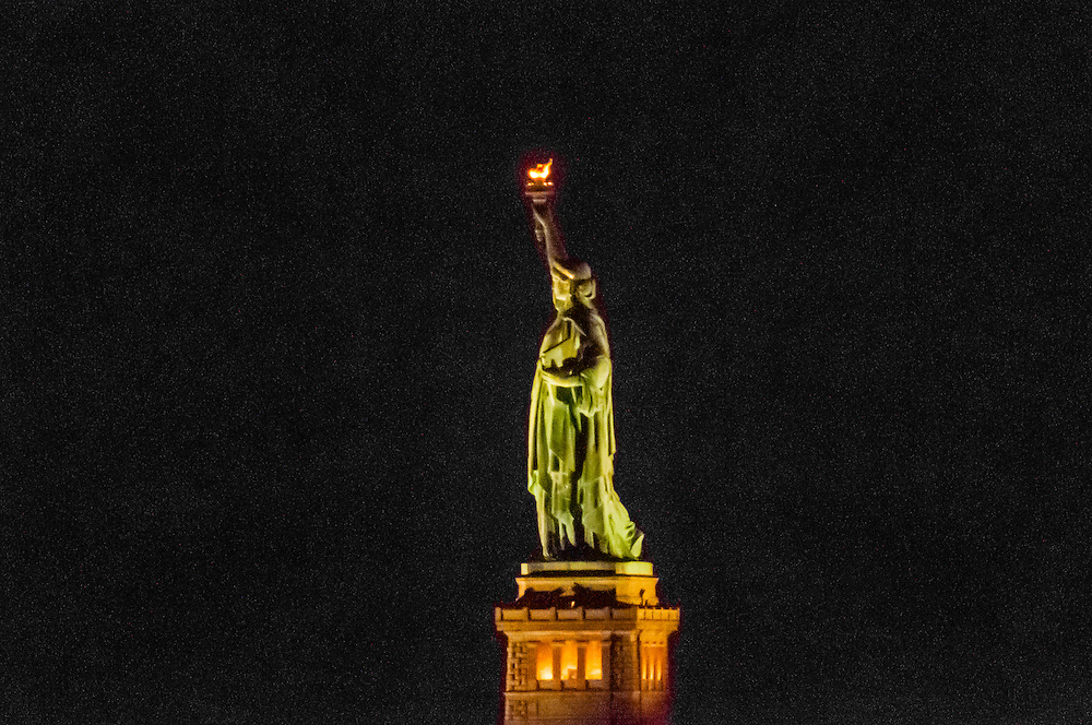 Statue of Liberty illuminated at night, New York Harbor, New York, New York USA.