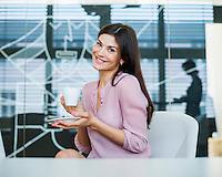 Portrait of confident businesswoman having coffee in office