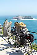 SANTANDER, SPAIN - April 18 2018 -  Bicycle parked against view over Bay of Santander and Mouro Island & lighthouse from a viewpoint on the Magdelena Peninsula, Cantabria, Northern Spain, Europe.