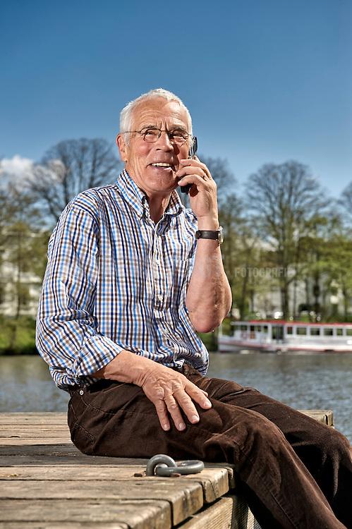 Älterer Mann sitzt auf einem Steg an der Alster in der Sonne