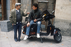 Young man sitting on parked scooter talking to older man,