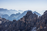 From Rifugio Guido Lorenzi on Monte Cristallo in the Ampezzo Dolomites, look northeast across blue ridges of the Sesto Dolomites (Dolomiti di Sesto, or Sexten/Sextner/Sextener Dolomiten). A lift to Forcella Staunies on Monte Cristallo gives unforgettable views over the Dolomites mountains (part of the Southern Limestone Alps) near Cortina d'Ampezzo, in the Province of Belluno, Veneto region, Italy, Europe. Monte Cristallo lies within Parco Naturale delle Dolomiti d'Ampezzo. Directions: From Cortina, drive 6km east on SR48 to the large parking lot for Ski Area Faloria Cristallo Mietres (just west of Passo Tre Croci Federavecchia). Take a chair-lift from Rio Gere to Son Forca (rising from 1698m to 2215m). Then take the old style ovovia (egg-shaped) Gondellift Forcella Staunies to Rifugio Guido Lorenzi (2932m) for astounding views. Climbers enjoy spectacular via ferrata routes here. Cortina gained worldwide fame after hosting the 1956 Winter Olympics. UNESCO honored the Dolomites as a natural World Heritage Site in 2009.