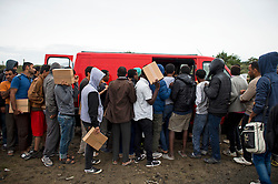 © London News Pictures. 11/08/2015. Calais, France. Migrants form a long queue to collect food being handed out by a charity within the migrant camp, know as 'The Jungle' in calais, France.  Photo credit: Ben Cawthra/LNP