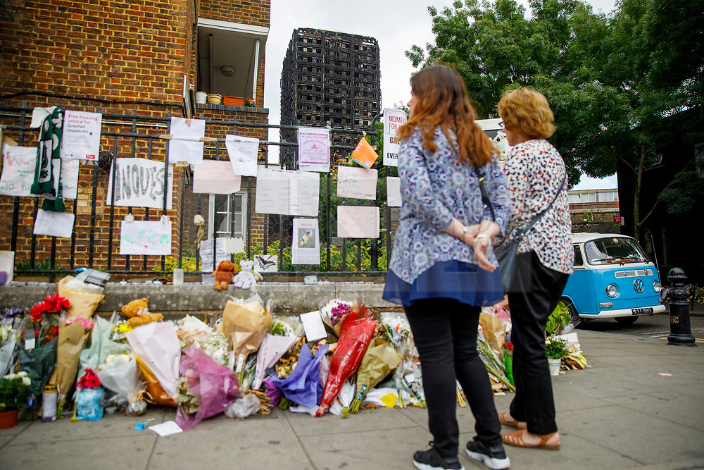 © Licensed to London News Pictures. 01/07/2017. London, UK. People look at the burnt Grenfell Tower and the missing posters on Saturday, 1 July 2017 on Latimore Road in west London. Photo credit: Tolga Akmen/LNP