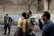 An Egyptian soldier hugs a protester as the military tries to establish a buffer zone between protesters and riot police during clashes November 22, 2011 near Tahrir square in central Cairo, Egypt. Thousands of protestors demanding the military cede power to a civilian government authority clashed with Egyptian security forces for a fourth straight day in Cairo, with hundreds injured and at least 29 protestors killed so far.  (Photo by Scott Nelson)