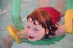 Young girl with hypotonia and associated learning difficulties swimming in public swimming pool using arm discs and hoop,