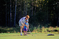 An instructor teaches a young boy, 4, to golf at the Pemberton Golf Course in Pemberton, BC Canada.