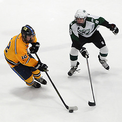 Staff photos by Tom Kelly IV<br /> Springfield's Tom Coll (12) skates with the puck around Ridley's Michael Giampapa (8) during the Springfield vs Ridley ice hockey game at Ice Works in Aston, Thursday night.