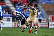 James McClean of Wigan Athletic looks to tackle Lewis Cook of Leeds United. Skybet football league championship match , Wigan Athletic v Leeds Utd at the DW Stadium in Wigan, Lancs on Saturday 7th March 2014.<br /> pic by Chris Stading, Andrew Orchard sports photography.