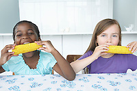 Two girls (5-6) sitting at table eating corn cobbs