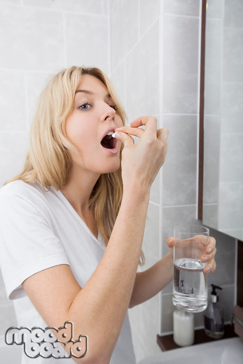Young woman taking medicine in bathroom