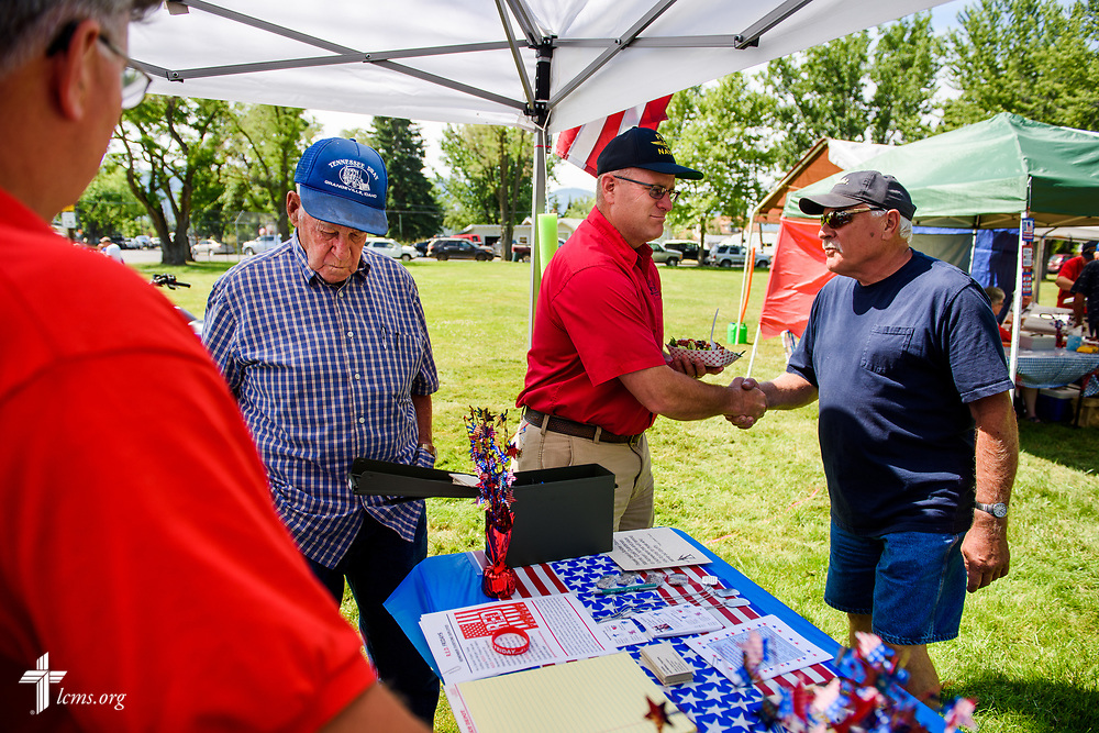 Paul Turpin (far left), a veteran and church member at Trinity Lutheran Church, Grangeville, Idaho, and the Rev. Michael Musegades (center), a fellow veteran and the pastor of the church, chat with visitors in the TLC4Vets outreach tent at the Grangeville Border Days Independence Day celebration and parade on Tuesday, July 4, 2017, in Grangeville. LCMS Communications/Erik M. Lunsford