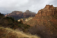 Stormy skies over Zion National Park, with bright sunbeams breaking through and snow capped mountains in the distance