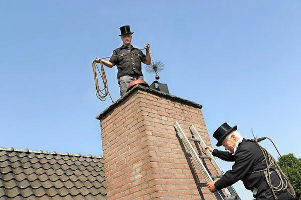 Nederland, Millingen, 26-7-2012Twee schoorsteenvegers, vader en zoon de Haan, vegen het rookkanaal van een houtkachel.Foto: Flip Franssen/Hollandse Hoogte.