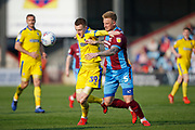 Wimbledon forward Joe Pigott (39)  and Scunthorpe United defender Byron Webster(5)  contest a loose ball  during the EFL Sky Bet League 1 match between Scunthorpe United and AFC Wimbledon at Glanford Park, Scunthorpe, England on 30 March 2019.